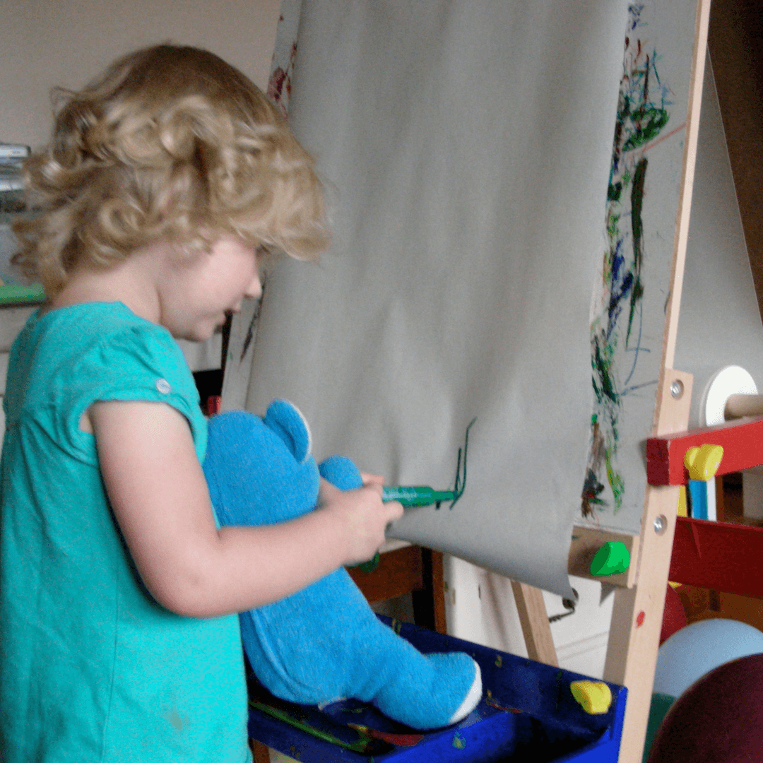 Image of a girl and her blue bear drawing on an easel