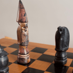 Image of four chess pieces - the king as the mediocre dad, a bishop, rook and knight, two of whom have the king in check.
