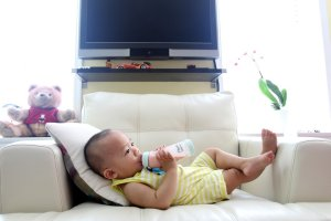 Toddler drinking milk, on couch