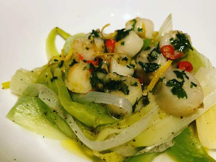 Fresh scallops with lemon and chilli butter served on a nest of leeks