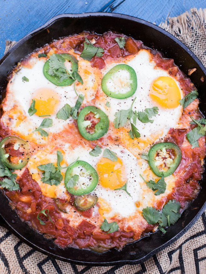 Eggs In Hell with some spice! Jalapeños added to diced tomatoes onions and garlic, topped with cheese and eggs. This is the ultimate comfort food!