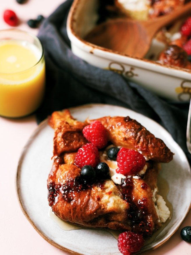 This cream cheese croissant french toast bake is topped with raspberry jam and served with fresh fruit. Can be prepped overnight and bakes in under an hour!