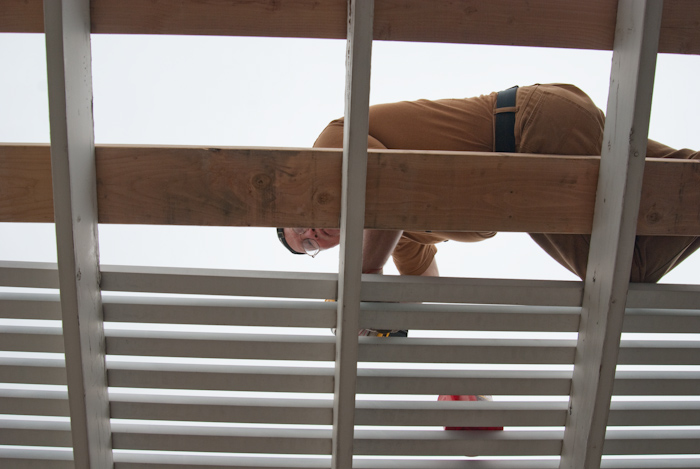 Gary taking apart patio cover, viewed from below