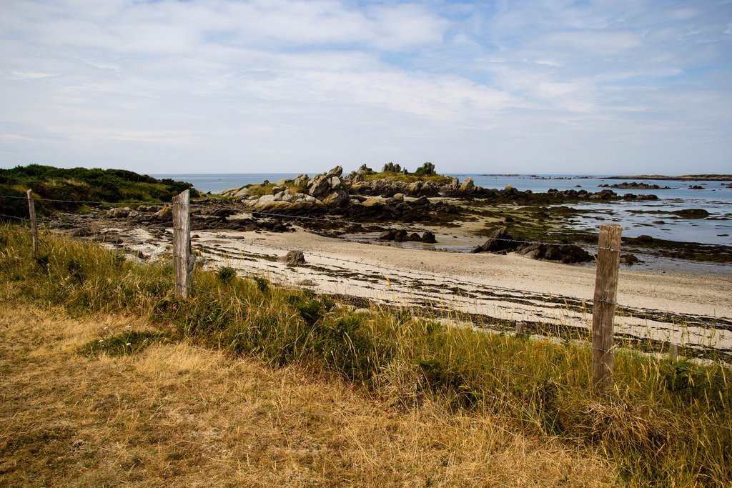 Rochers et plage de sable blanc.