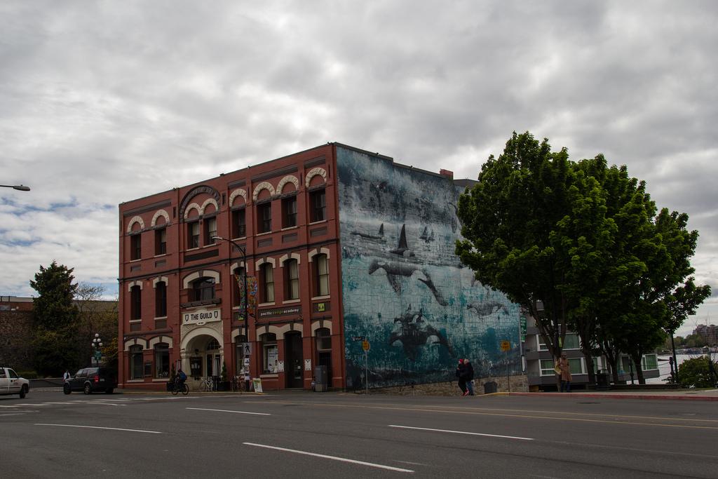 Bâtiment de briques ocre et fresque murale.