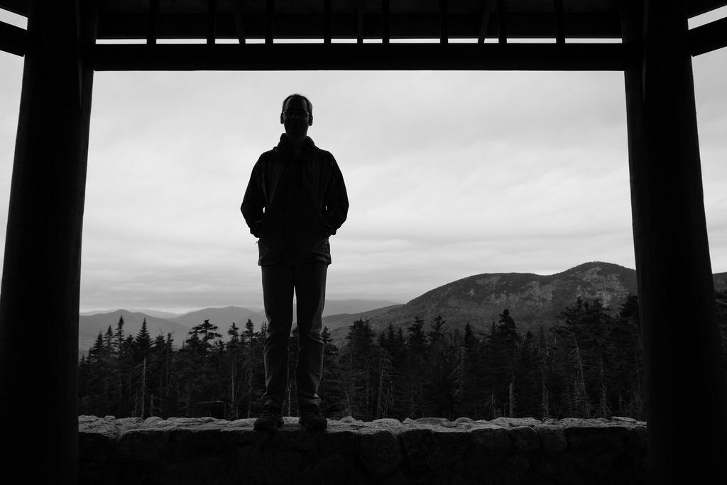 Silhouette en Noir et Blanc, sur fond de forêt et sommets.
