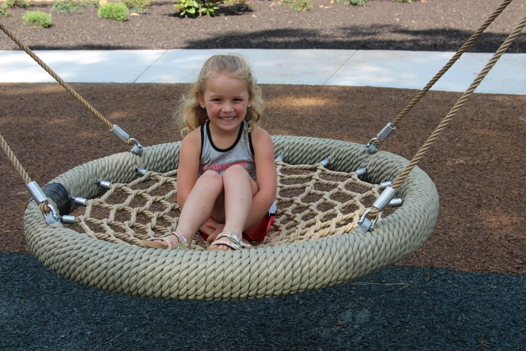 A blonde young girl sits in the Cloud 9 swing. She is wearing a grey shirt and red shorts.