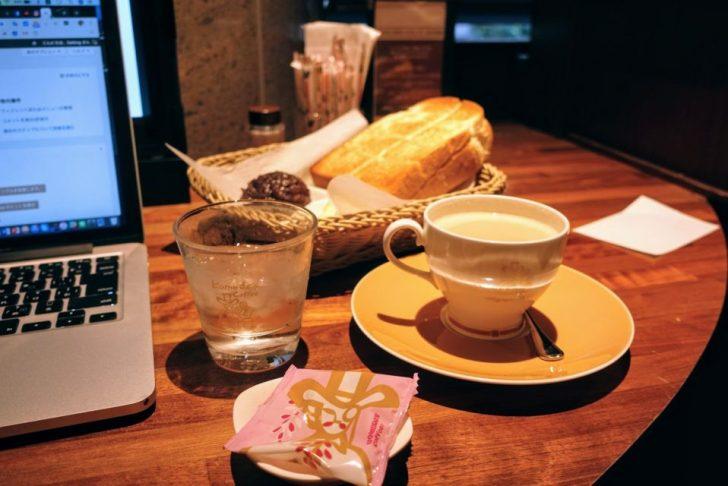 コメダ珈琲の机の上にある前に水とミルクコーヒーと奥にある小倉トースト