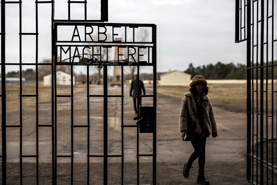Посетители проходят мимо входных ворот в лагерь смерти Освенцим, самый печально известный из многих нацистских концлагерей. Getty