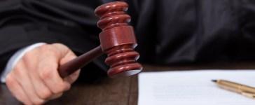 Judge giving verdict by hitting mallet at desk. (Shutterstock/Andrey Popov)