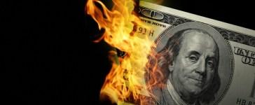 Money on fire. Photo: Shutterstock