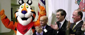 """NEW YORK, UNITED STATES: """"Tony the Tiger"""" celebrates the Kellogg Company's acquisition of the Keebler Foods Company by joining New York Stock Exchange Chairman Richard Grasso (2nd from L), Kellogg Chairman and CEO Carlos Gutierrez (2nd from R), and Keebler CEO Sam Reed (R) on the bell podium at the start of the trading day 27 March 2001. Kellogg's, the world's largest producer of cereal, recently acquired Keebler, the second largest producer of crackers and cookies in the U.S. HENNY RAY ABRAMS/AFP/Getty Images"""