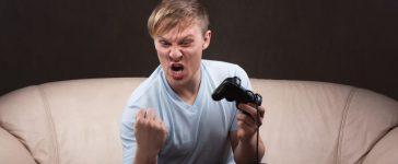 Young man enthusiastically playing video games. [Shutterstock - Sanzhar Murzin]