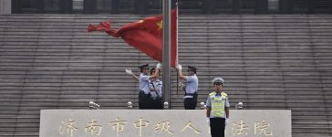 Policemen hoist a Chinese national flag in front of an entrance of a Chinese court. REUTERS/Aly Song