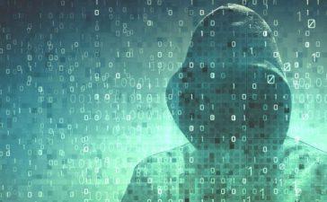 Hacker over a screen with binary code. [Shutterstock - adike]