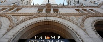Flags fly above the entrance to the new Trump International Hotel on it's opening day in Washington September 12, 2016. REUTERS/Kevin Lamarque