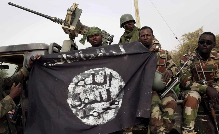 Nigerian soldiers hold up a Boko Haram flag that they had seized in the recently retaken town of Damasak, Nigeria