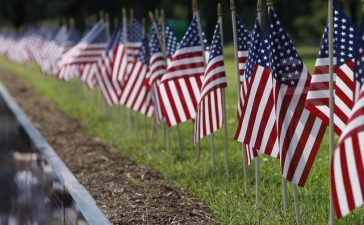 American flags are placed on the top of the Vietnam Veterans Memorial wall, etched with the names of more than 58,000 U.S. servicemen and women who died in the war, on Memorial Day in Washington May 28, 2012. REUTERS/Yuri Gripas.