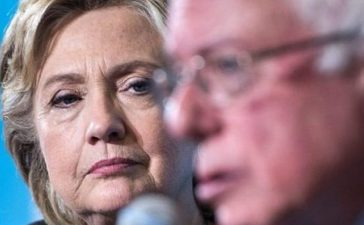 Democratic presidential nominee Hillary Clinton listens as Senator Bernie Sanders (I-VT) speaks during an event at University of New Hampshire September 28, 2016 in Durham, New Hampshire
