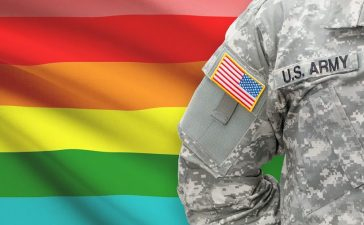 Servicemember standing in front of an LGBT flag. Niyazz/Shutterstock.