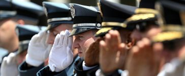 DALLAS, TX - JULY 13: Police officers salute during funeral services for slain Dallas Area Rapid Transit (DART) police officer Brent Thompson at the Potter's House Church on July 13, 2016 in Dallas, Texas. DART police officer Brent Thompson was one of five Dallas police officers who were shot and killed by a sniper during a Black Lives Matter march in Dallas. (Photo by Justin Sullivan/Getty Images)