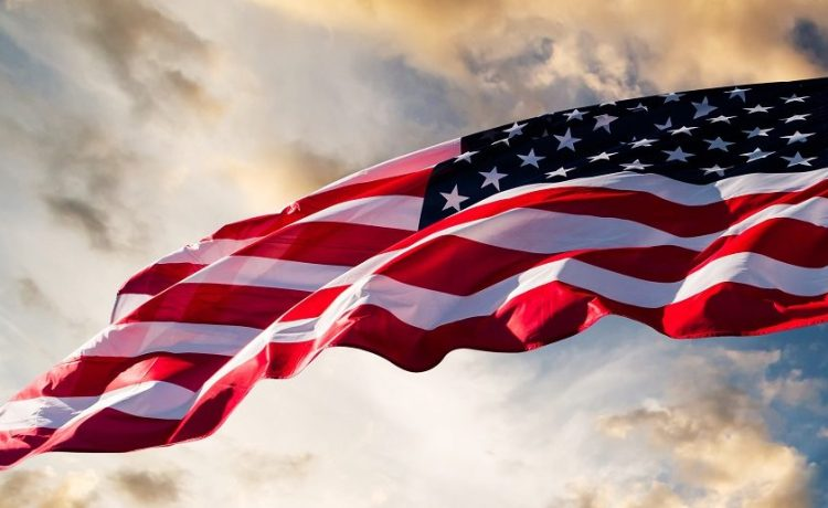 An American flag against a sky background. (Green/Shutterstock)