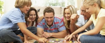 Family plays a board game (Photo via Shutterstock)