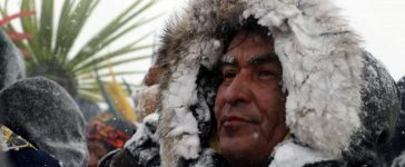 """A Native American man stands in the snow during a march with veterans near Backwater Bridge just outside of the Oceti Sakowin camp during a snow fall as """"water protectors"""" continue to demonstrate against plans to pass the Dakota Access pipeline adjacent to the Standing Rock Indian Reservation, near Cannon Ball, North Dakota, U.S., December 5, 2016. REUTERS/Lucas Jackson"""