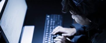 Hooded computer hacker stealing information with laptop. [Shutterstock - PORTRAIT IMAGES ASIA BY NONWARIT]