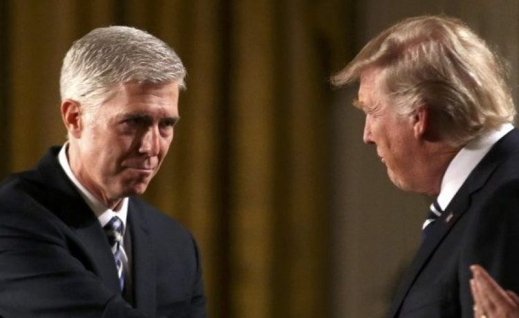 Judge Neil Gorsuch (L) shakes hands with U.S. President Donald Trump as Gorsuch's wife Louise (R) applauds after President Trump nominated Gorsuch to be an associate justice of the U.S. Supreme Court at the White House in Washington, D.C., U.S., January 31, 2017. REUTERS/Carlos Barria