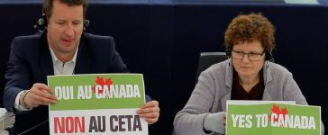 """French politician Yannick Jadot (L), green party EELV (Europe-Ecologie-les-Verts) candidate for the 2017 French presidential election and Member of the European Parliament sits behind a placard that reads """"Yes to Canada, No to CETA"""" as he waits for the start of a voting session on the Comprehensive Economic Trade Agreement (CETA) between the EU and Canada, in Strasbourg, France, February 15, 2017. REUTERS/Vincent Kessler"""