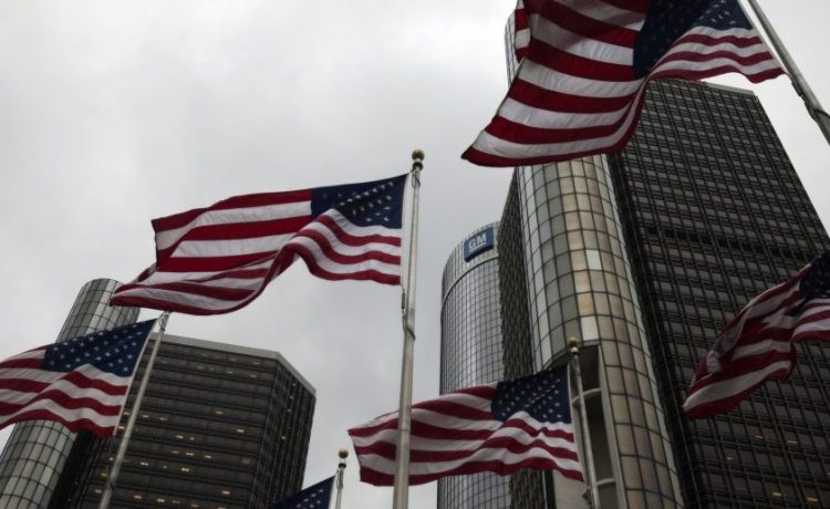 Flags wave in front of the General Motors Corp world headquarters in downtown in Detroit, May 28, 2009. General Motors Corp persuaded its major bondholders to accept a sweetened ownership plan on Thursday, a deal that could result in a smoother ride for the carmaker through bankruptcy. REUTERS/Mark Blinch