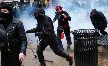 Masked 'Black Bloc' members race after being hit by a stun grenade while protesting against Trump on the sidelines of the inauguration in Washington. REUTERS/Adrees Latif.