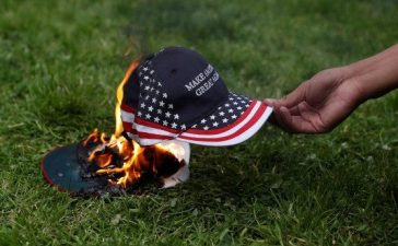 "A demonstrator in opposition of President Trump sets a hat on fire during a ""People 4 Trump"" rally in Berkeley, California. REUTERS/Stephen Lam"