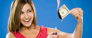 Woman setting American one dollar bill on fire (Shutterstock/Alan Bailey)