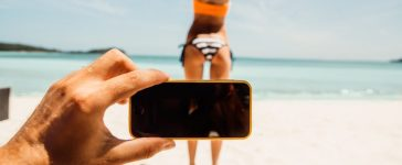 Man taking a photo of a woman in a bikini on the beach. [Shutterstock - Nikkolia]