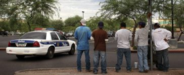 Undocumented immigrants stand on a curbside awaiting day labor work as a police patrol passes by July 26, 2010 in Phoenix, Arizona. (Photo by John Moore/Getty Images)