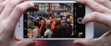 A spectator takes a picture on her cell phone of Canada's Prime Minister Justin Trudeau at a Chinese New Year parade in Vancouver, B.C., Canada January 29, 2017. REUTERS/Ben Nelms