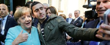 FILE PHOTO: Syrian refugee Anas Modamani takes a selfie with German Chancellor Angela Merkel outside a refugee camp near the Federal Office for Migration and Refugees after registration at Berlin's Spandau district, Germany September 10, 2015. A German court will on February 6, 2017 hold its first hearing in the case of a Syrian refugee who is suing Facebook after the social networking site declined to remove all posts linking him to crimes and militant attacks. REUTERS/Fabrizio Bensch/File Photo