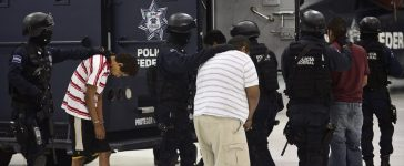"""Alleged members of the gang """"Cartel Independent from Acapulco"""" are taken into an armored vehicle after being presented to the press with the alleged leader Jos? Alberto Quiroz P?rez (out of frame), aka """"Juan Diego"""", in Mexico City on September 6, 2012. Quiroz P?rez was arrested in Acapulco, Guerrero State, on September 5. Ronaldo Schemidt/AFP/Getty Images."""