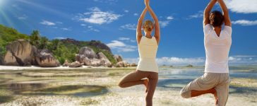 fitness, people and recreation concept - couple doing yoga in tree pose from back over exotic tropical beach background (Shutterstock/Syda Productions)