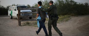 A U.S. border patrol agent detains a man after entering the United States by crossing the Rio Grande river from Mexico, in Roma, Texas, U.S., May 11, 2017. (PHOTO: REUTERS/Carlos Barria)