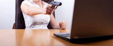 Woman frustrated with computer error, takes aim with her firearm. [Shutterstock - Peter Bernik]