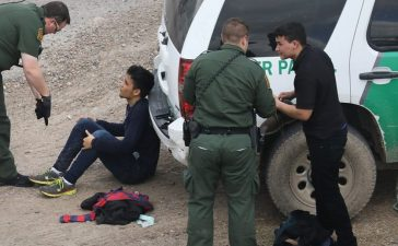U.S. Border Patrol agents detain two undocumented immigrants after capturing them near the U.S.-Mexico border on March 15, 2017 near McAllen, Texas. U.S. Customs and Border Protection announced that illegal crossings along the southwest border with Mexico dropped 40 percent during the month of February. (Photo by John Moore/Getty Images)