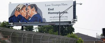 Bicyclists ride past a billboard depicting a kiss between Donald Trump and Ted Cruz on the first day of the Republican National Convention on July 18, 2016, in Cleveland, Ohio. (Photo: DOMINICK REUTER/AFP/Getty Images)