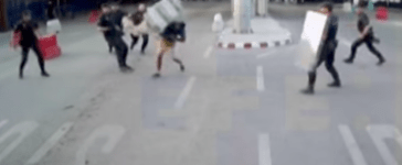A Spanish police officer knocks out a knife-wielding man with a plastic road barrier. (Juan Ignacio Zoido/screenshot from Twitter)