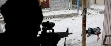 """An Iraqi special forces soldier shoots dead a would-be Islamic State suicide bomber in Mosul, Iraq, March 3, 2017. Goran Tomasevic: """"I was accompanying an Iraqi counter-terrorism military unit into a district of western Mosul held by Islamic State. I had spent some time """"embedded"""" with the counter-terrorism force so they allowed me to follow their advance. We were moving on foot through side streets, with soldiers searching house-to-house to clear the way. Turning a corner into a more exposed main street, we suddenly came under heavy fire from IS, which forced us to race inside a nearby house for cover. In so doing, a soldier near me was fatally shot in the back, while once inside the house another was shot in the head by a sniper as I was speaking with him. We were in a dangerous situation, pinned down by IS fire, though the militants were kept back for the time being by air strikes called in by the unit commander, plus intensified mortar fire from our side. Hours passed by and daylight faded to night. Suddenly soldiers near me began shouting, shooting broke out and I saw one soldier shooting a would-be IS suicide bomber trying to approach the house door. I took the picture seconds later standing just behind the shooter in silhouette, with the suicide bomber visible through a shell hole in the house wall, dead on the ground in a spreading pool of blood. It was pretty heavy stuff, extremely close-range war fighting. But I have covered the front lines of many wars so I just stay calm in these tough spots and think only how I can shoot the best pictures while seizing the right moment to pull back out of harm's way. This time, we had to wait until just after dawn the next day to retreat, darting from one street corner to the next to reach safety back behind the front lines."""" REUTERS/Goran Tomasevic/File photo."""