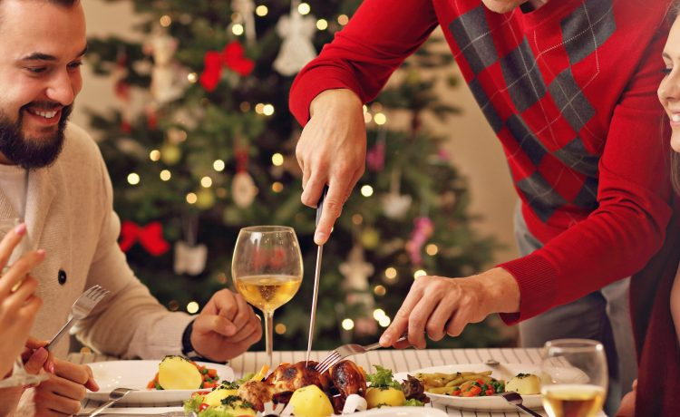 A family eats Christmas dinner. (Shutterstock/Kamil Macniack)