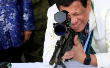 "FILE PHOTO - Philippine President Rodrigo Duterte checks the scope of a 7.62mm sniper rifle during the turnover ceremony of China's urgent military assistance given ""gratis"" to the Philippines, at Clark Air Base, near Angeles City, Philippines June 28, 2017. REUTERS/Romeo Ranoco/File Photo"