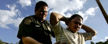 U.S. Border Patrol agent, Eli Vasquez (L), checks an illegal alien for contraband August 30, 2005 in Nogales, Arizona. The governors of New Mexico and Arizona have declared a state of emergency along the border due to drug trafficking, illegal immigration and terrorism. (Photo by Sandy Huffaker/Getty Images)